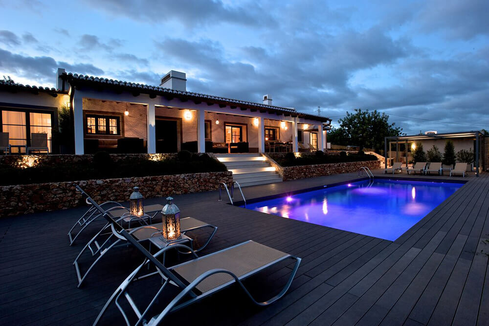 This luxurious property has a regular pool in the backyard with several loungers.