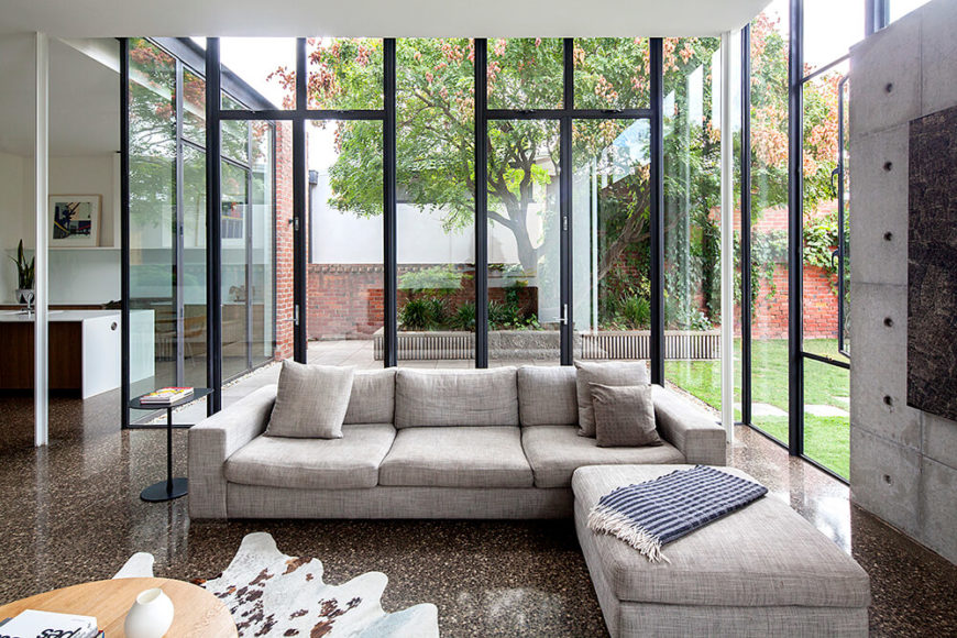 The living room, anchored by the singular concrete wall at right, centers on a contemporary sectional and natural wood coffee table. This space sits almost entirely wrapped in glass, creating an expansive sense of surroundings.