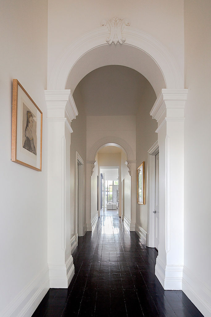 This lengthy hallway connects the original and additional parts of the home, with a timeless elegance. This space blends the white minimalism of the modern addition into the more ornate look of the older structure.