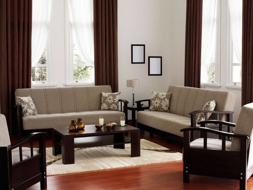 In this living room there is a simple and elegant color palette with matching minimal sofas. These simple sofas with their dark woodwork and wide, comfortable seats are welcoming and work well for a more modern design.