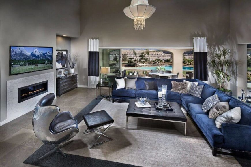 This is an example of a more typical sectional sofa. The seating is ample, and it curves in an L-shape around this living room. The majority of the seats face the television, and there is a large square table in the center that can be easily used by nearly all of the seated occupants.