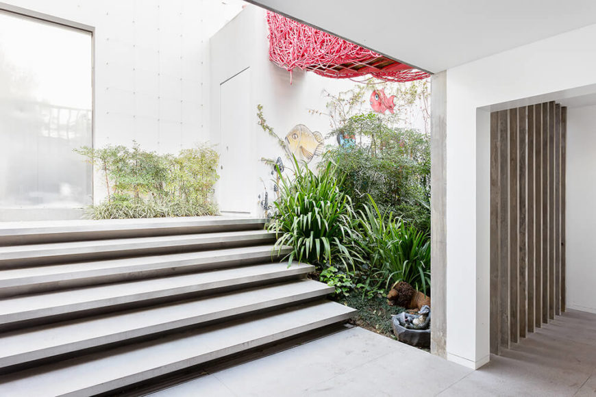 Here we see the stairs and bridge between the two buildings from inside the large open space room. Subtle accents like natural wood planks and an aquatic wall painting speak volumes.