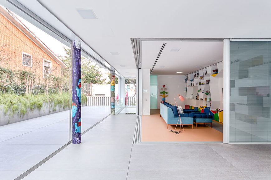 Viewed from outside, we can see how the retractible glass panels fully open to connect the indoors and outside. Built-in shades make the room a snap to privatize.