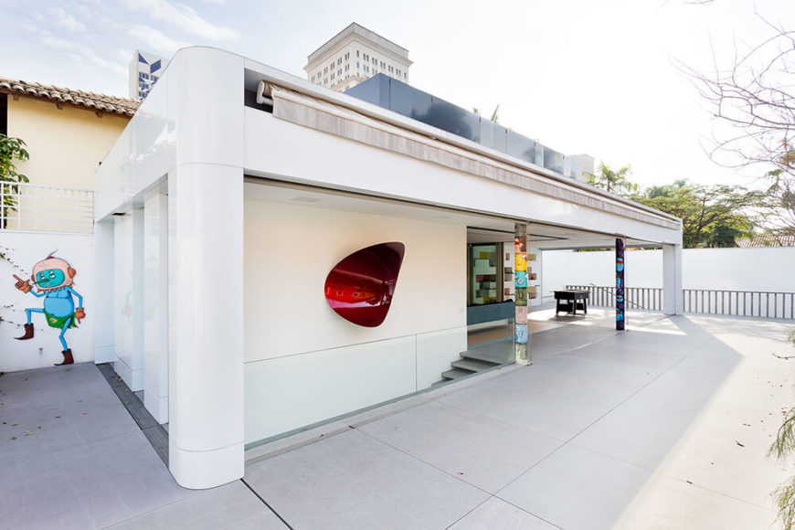 With a wide exterior view, we can see many of the colorful artworks adorning the Toy House, enlivening the white facade with personality and color. Here, we can see the full length awning that can be pulled down to shade the structure.