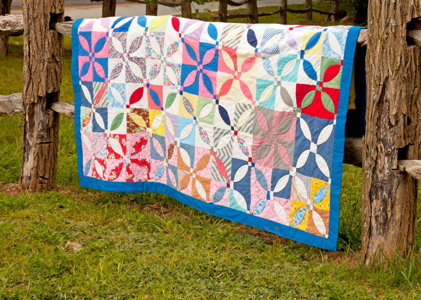 Quilt hanging on a wooden fence quilt stand
