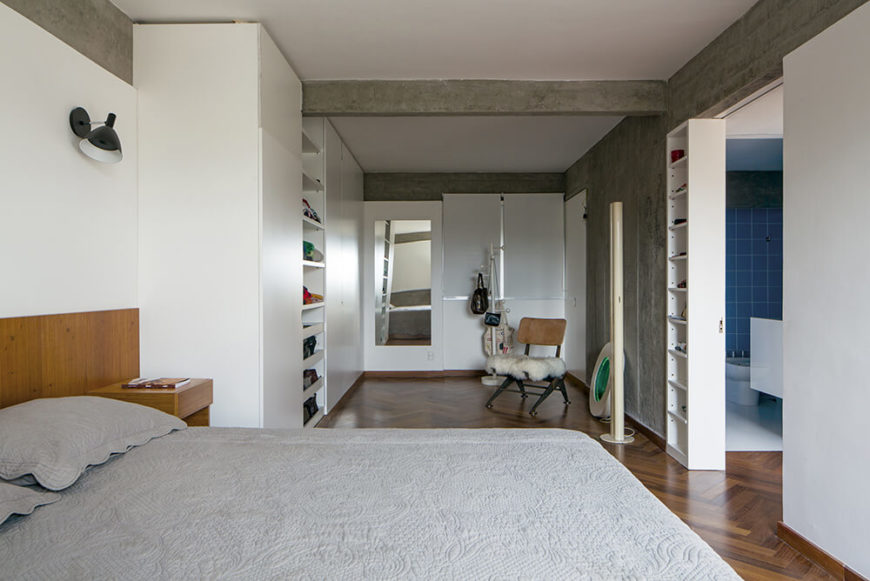 The primary bedroom features a lengthy relaxing space beyond the bed, with built-in shelving for clothes and other items. A singular wooden chair with a white fur seat stands in the open space.