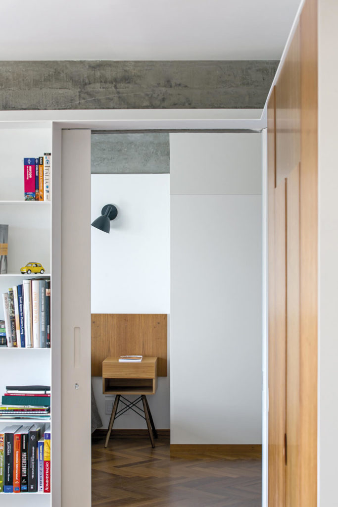 Beyond the living room, we see the passage toward the bedrooms. The hardwood flooring continues here, as we see a midcentury modern bedside table in bright natural wood.