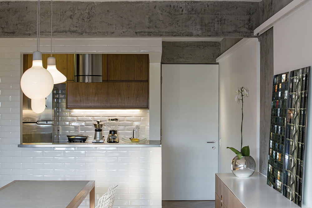 This industrial kitchen features white walls and countertops. The pendant lights are just so attractive.