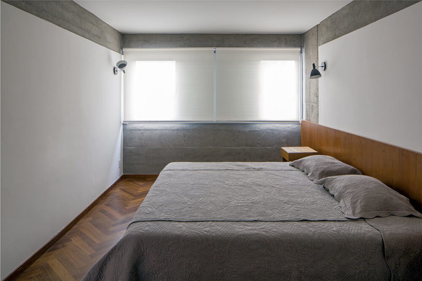 Viewed in the other direction, we see the concrete wall poking out in the bedroom, flanked by white walls on one side and a room-wide wooden headboard on the other.