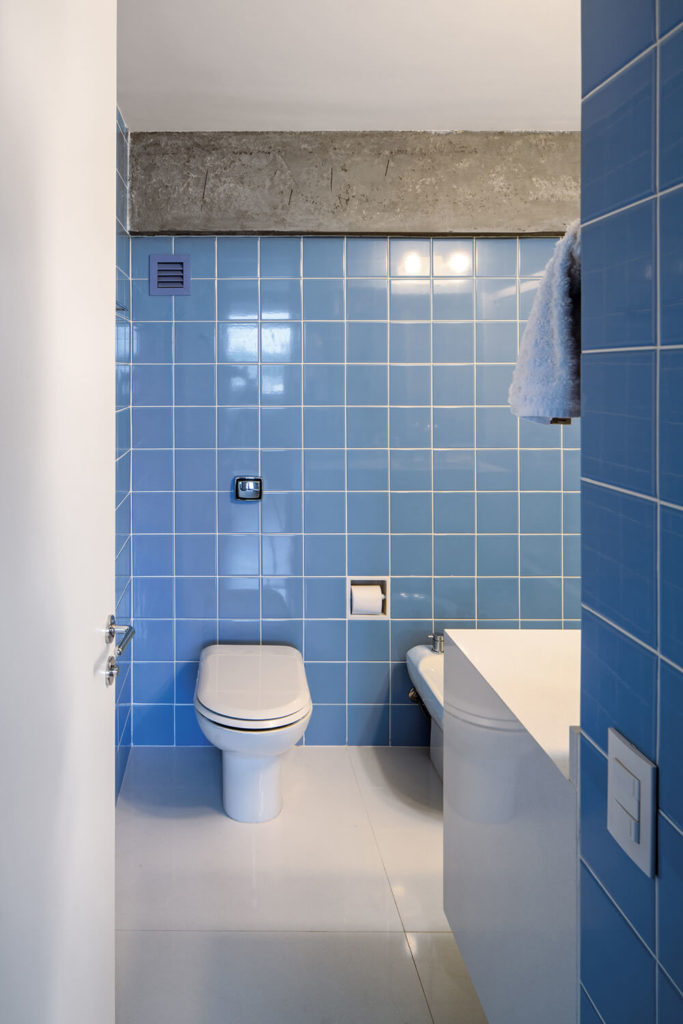Here's the primary bath, standing apart within the apartment with its use of bright blue wall tiles. Even here, the concrete structure makes its presence known.