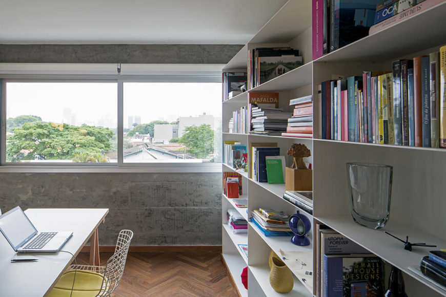 With a closer look at the shelving, we see how the thin materials add contrast to the space, opposing the thick concrete slabs of the walls. The thin, white-topped natural wood writing desk is another great minimalist touch.