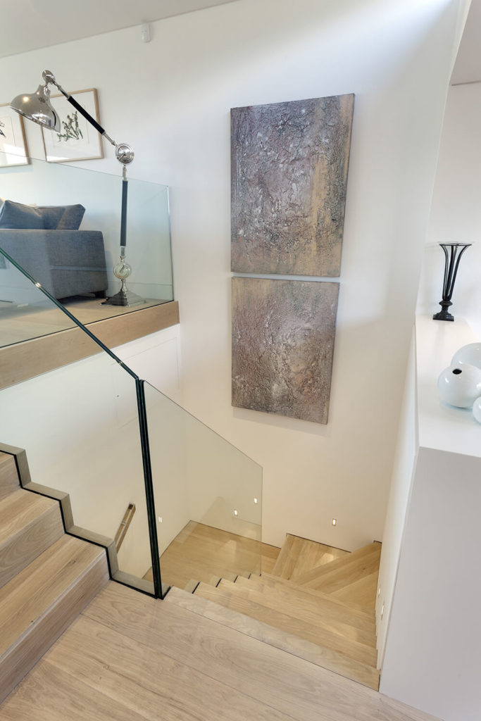 Moving down the natural wood stairs from the living room, we see how the frameless glass balustrade keeps visual lines open throughout the home. The open, airy nature of these elements helps the compartmentalized space feel more expansive.