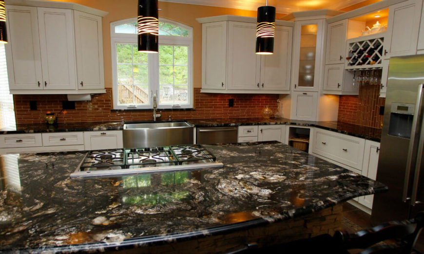 3-ultimate-granite-guide The veining and circular patterns of this dark brown granite draw the eye to the large kitchen island. A red glass tile backsplash pulls warmer colors out of the darker granite, while the white cabinetry keeps the kitchen bright and airy.