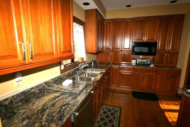 This darker granite relies on lighter streaks to bring in warmer tones from the oak cabinets and the paint color.