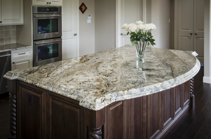 Another rich cream granite with light brown and black veining. A stacked edge and a gentle curve on one edge are incredibly elegant. A simple glass vase with white roses is the perfect accompaniment.