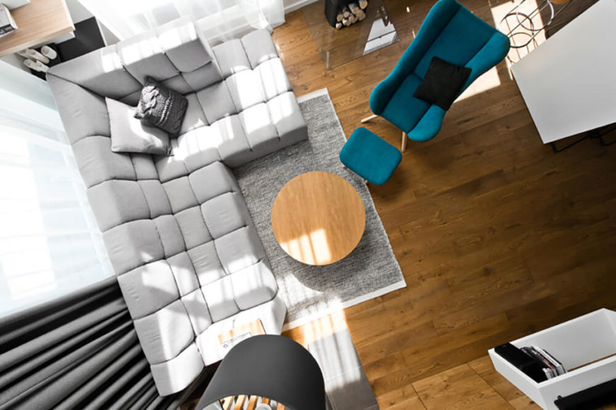 In this overhead view of the living room, we can readily see the balanced arrangement of tasteful furniture, with a neutral set of tones against the rich hardwood flooring. A single blue armchair and ottoman offer a burst of color in this room.