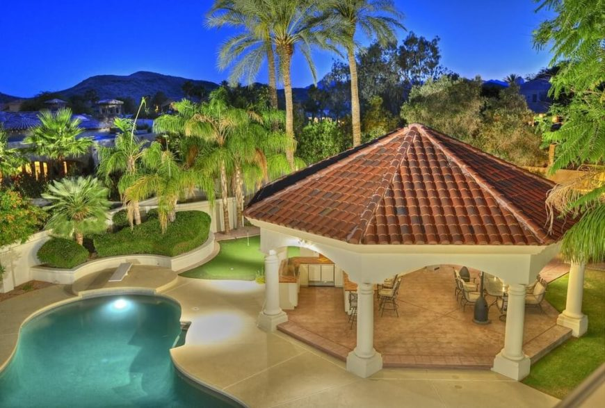 his stone pavilion with a tiled roof is a fantastic partner to this pool area. The patio area is a welcoming and fun spot for any gathering.