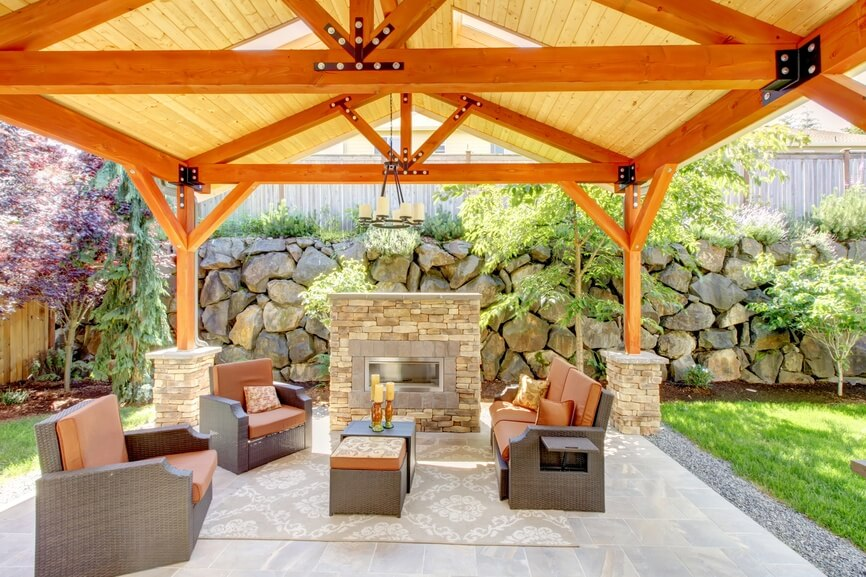 This pavilion is built with highly finished wood and has small stone foundations. This design is great for the modern and simple furniture that sits around the stone fireplace underneath.