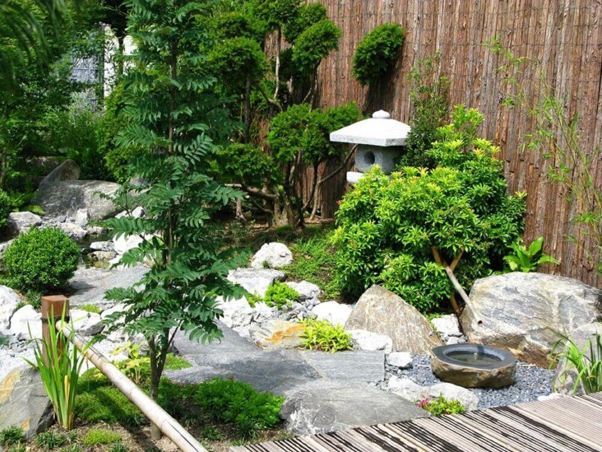Rock garden with bamboo fence and water feature.