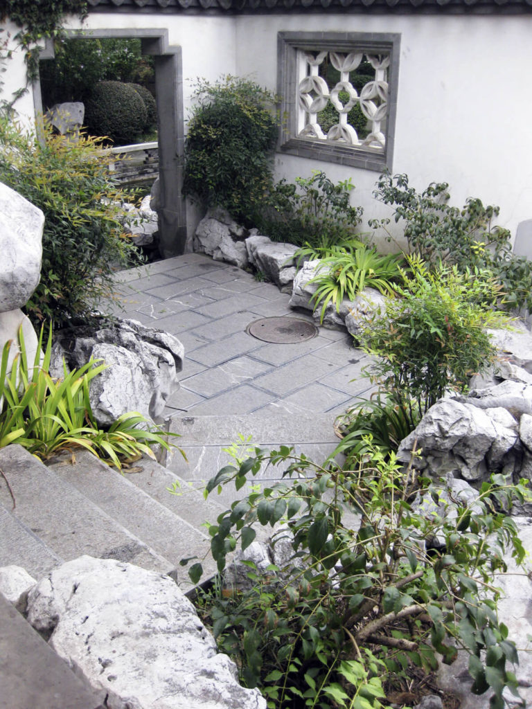 Here we see a concrete stairway leading to a small patio and archway. The rocks here line the patio and walkway. They divide the plants from the walkway, creating a visually interesting and creative natural barrier.