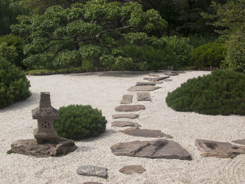Stepping stones are perfect for a zen garden such as this. Zen gardens are made of sand that can be raked and manicured. This look is paired well with large stepping stones and rocks. They give passersby a way through the garden without disturbing the work of the organized sand.