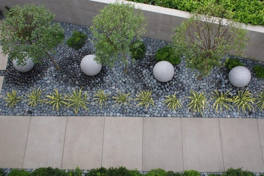 Small stones make a great bed for a garden. These small stones reduce the amount of dirt that gets everywhere and also cut down on weed growth. While you may choose the natural look of rough stone, round and polished stone gives a different feel.