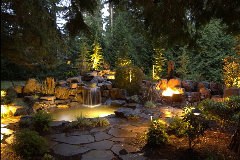 Pairing your garden lights with other lighting features can tie together your garden theme. Here we see the well lights in the garden matching both the underwater lighting fixtures and the path lighting.
