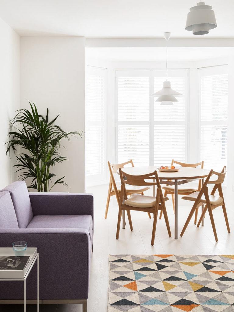 The dining area is part of the larger open plan space at the center of the home. Here we see how elements like the natural wood dining set, contemporary purple sofa, and multicolored rug offer texture and variety in the white space.