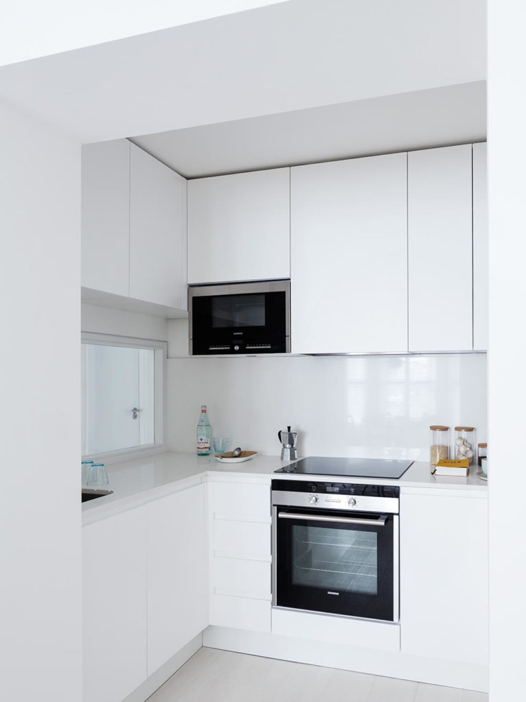 The kitchen is packed with storage options, courtesy of sleek white cabinetry that runs the full height of the space. A minimalist streak makes for a compelling, singular room.