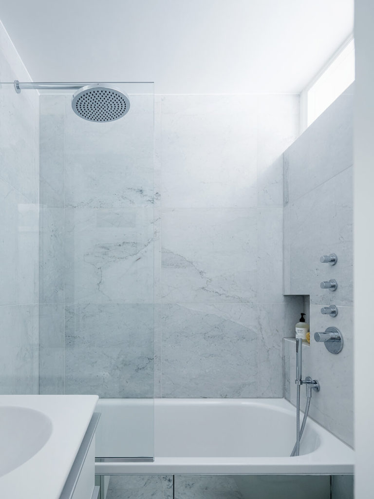 The primary bath is awash in white marble, adding a hearty textural element to the white minimalist look. A large soaking tub is framed in glass, while a slim upper window offers some sunlight to the room.