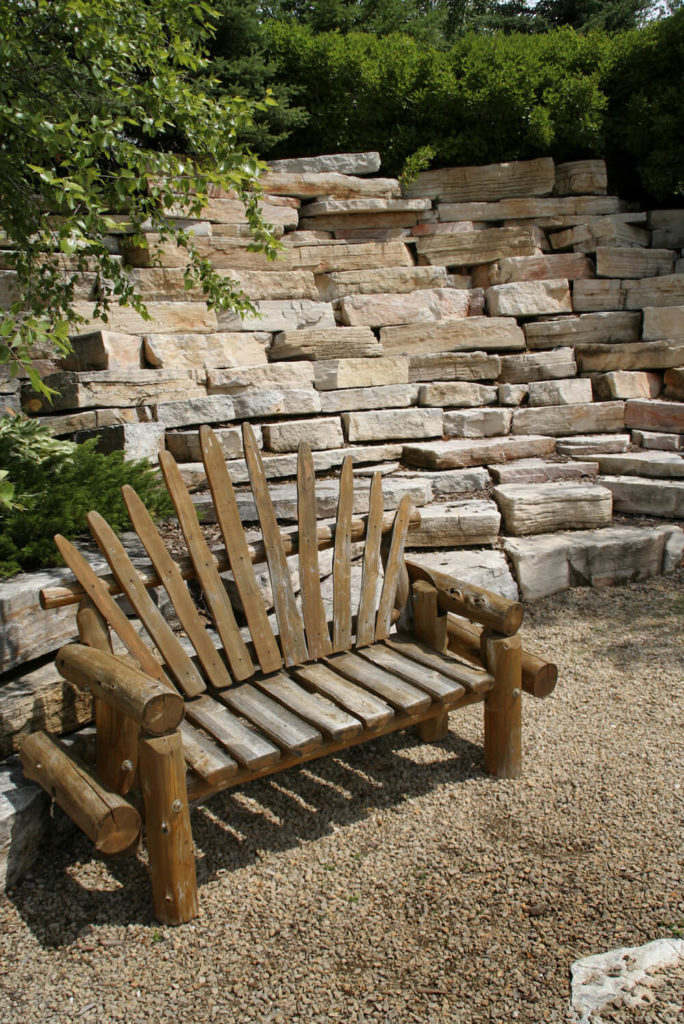 Using wood gives a bench a very natural feel. This bench is made from nearly raw tree branches. This is a method that produces a very natural looking, yet still crafted, piece.