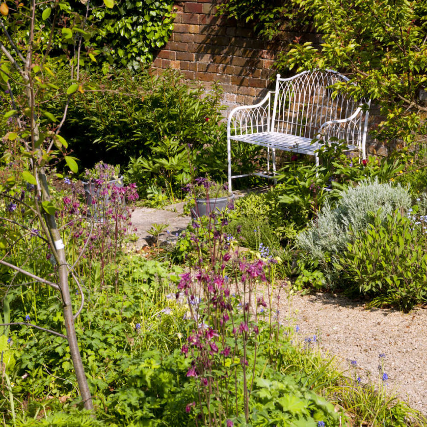 Here is a simple metal bench that is painted white. It doesn't blend with the surroundings, but instead brings a lightness to the area. The contrast against the greenery works in this garden.
