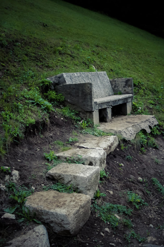 Here is a stunning and isolated stone bench in the side of a hill. This stone bench has a great patina. The mossy surroundings give this entire area an aged feel that is quite appealing.