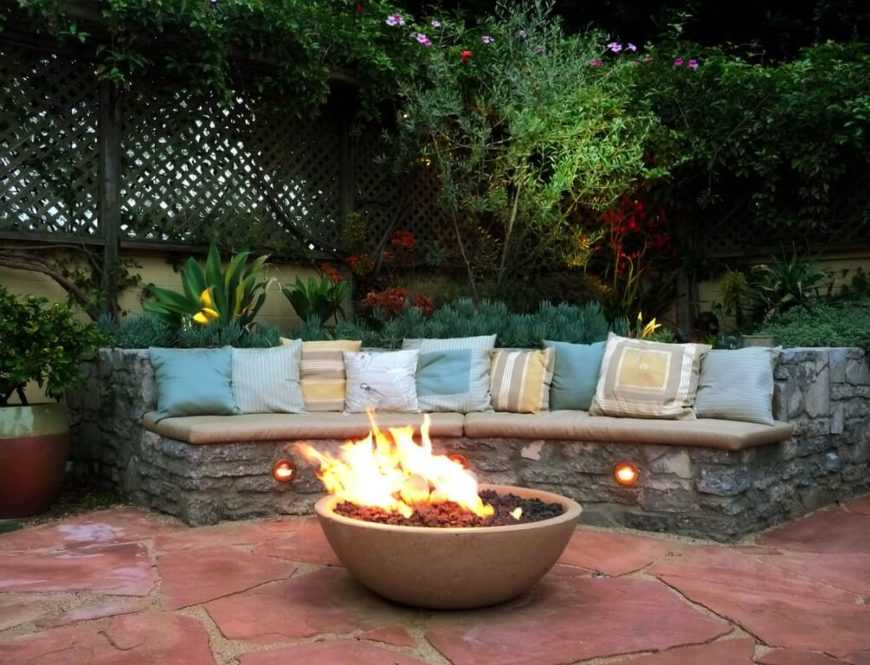 A curved bench is a great idea to put around a fire pit. With a bench like this everyone on the bench can face the fire together and still all sit together. While this bench is stone, a simple cushion and some pillows makes it far more welcoming and comfortable.