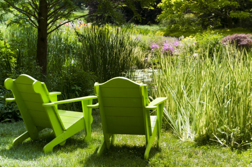 Spring green adirondack chairs overlooking a pond.