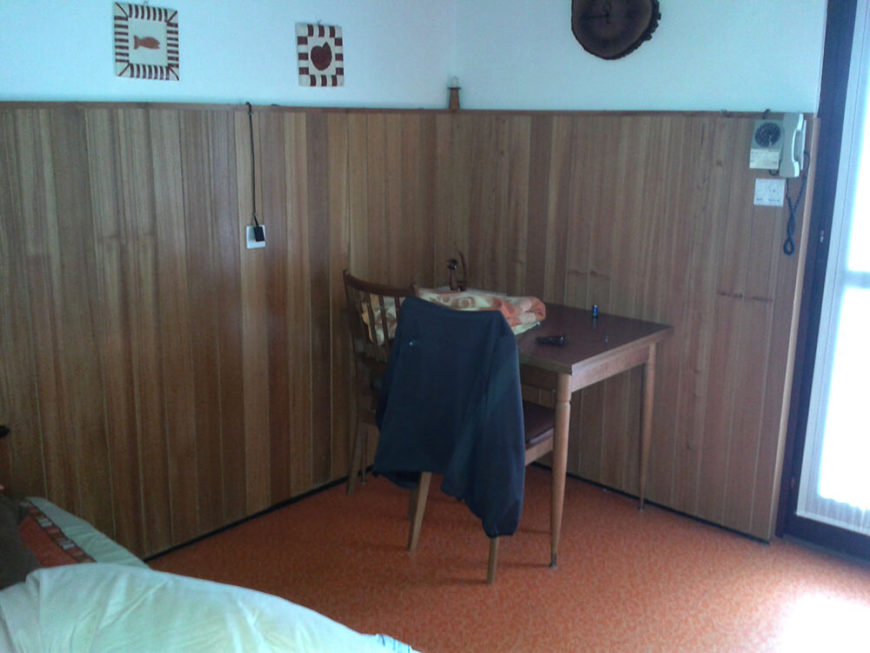 The living room area was dated by dark walls and wooden paneling in addition to the red cork flooring. A blanket covered sofa looked dingy.