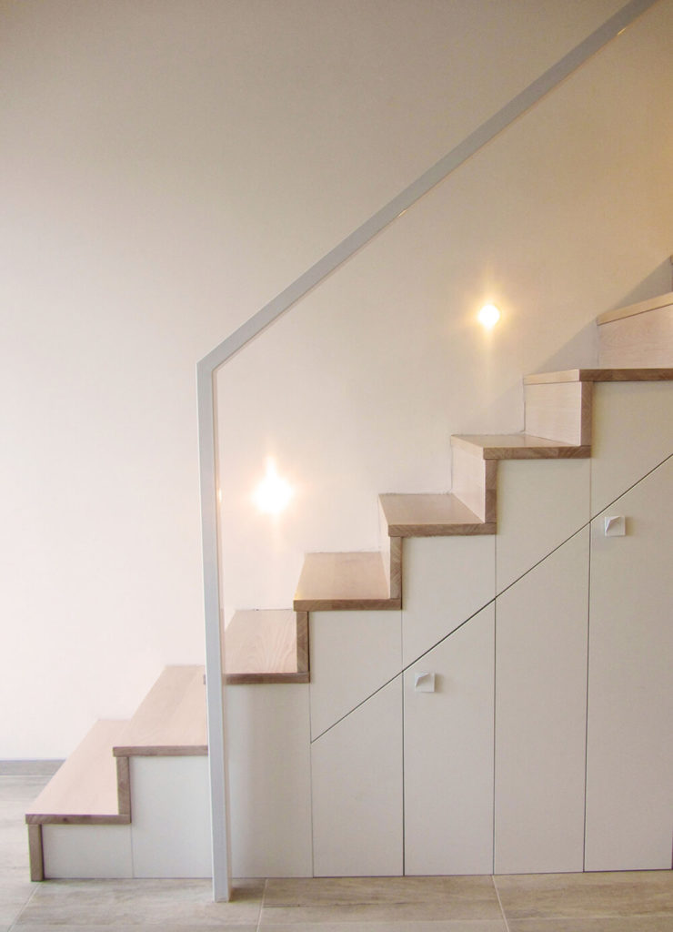 Heavy black railings were replaced by a white railing and light wood treads. The result is a light, bright, and spacious stairway.