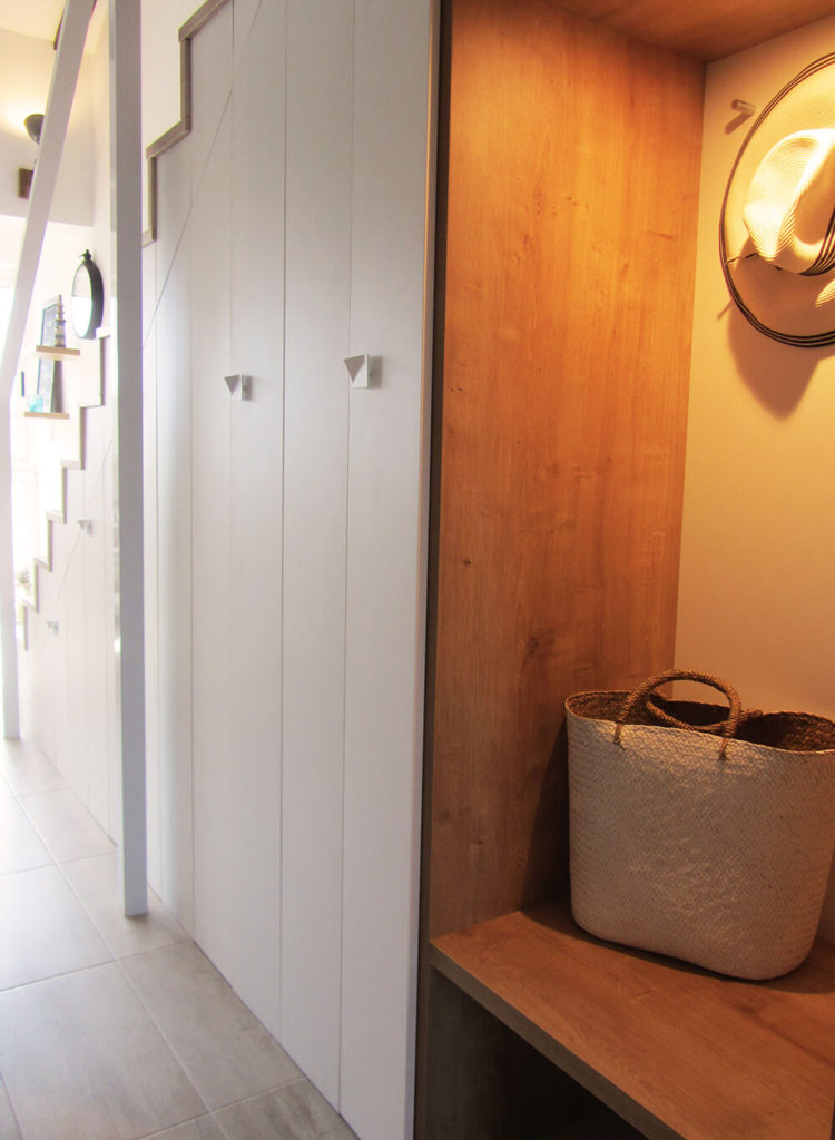 As we move past the mirrored closet we can see the wooden bench area that's the perfect place to hang a hat or set a purse after coming in the door. Space under the stairs has been turned into clever storage.