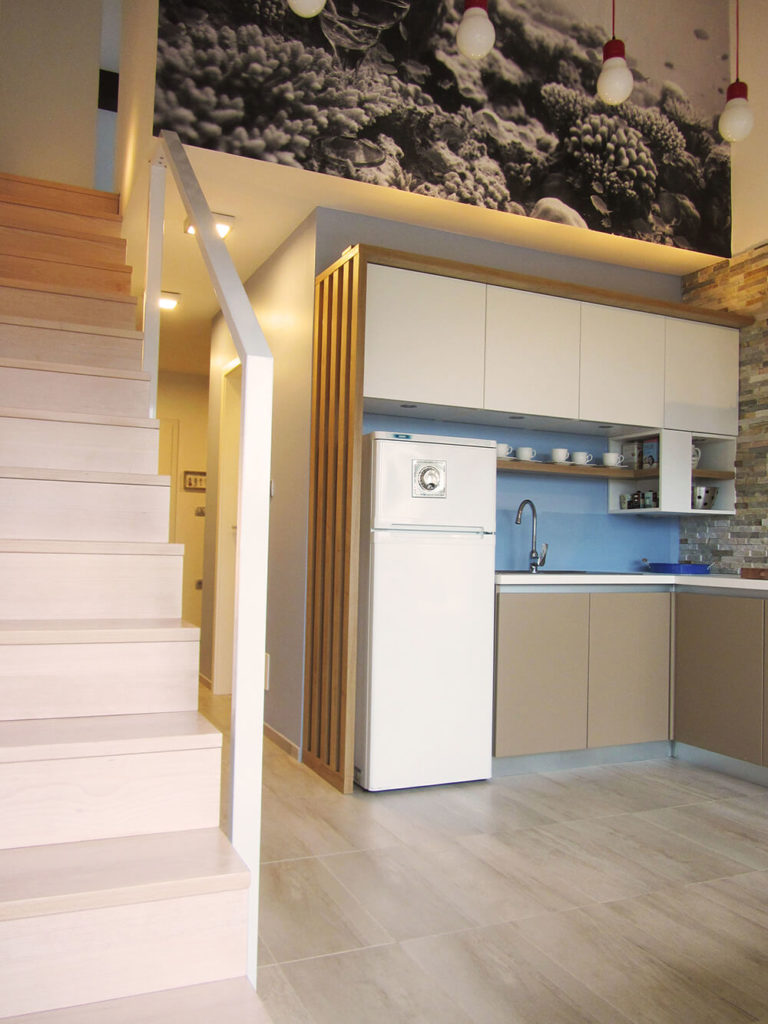 The entry hall ends in the kitchen area, which has been fully renovated with sleek, minimalistic cabinets. The blue wall, backsplash, and an adjacent layered stone facade bring warmth into the simple design.