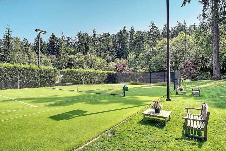 Here is a court with wonderful hedges around the outside and some nice benches for watching matches. The grass top court is great for a verdant and manicured lawn.