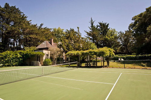 A simple fence and some bushes do just as well to border your tennis court. The greenery brings a bit of character and the simple fence catches runaway balls without disrupting the view.