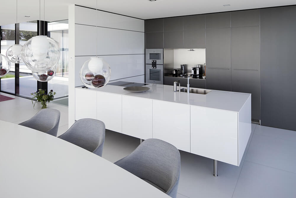 Modish kitchen with smooth white counters and countertops matching the white tiles flooring. The pendant lights look glamorous.