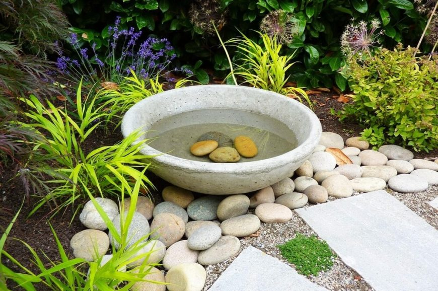 Here is a carved stone bird bath with some stones in the water. This provides a manufactured feel with more natural textures.