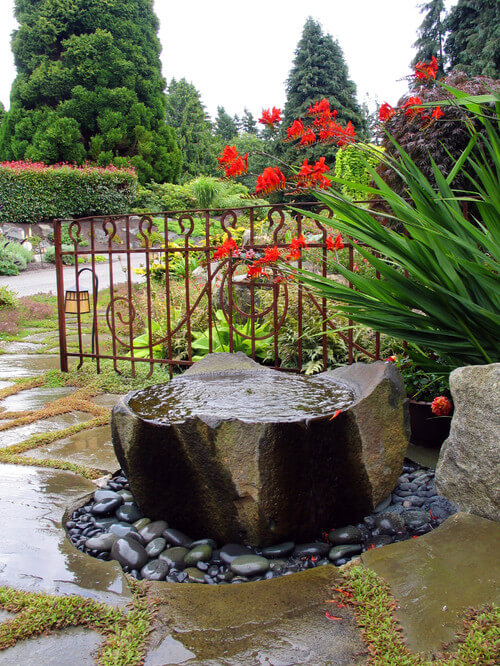 Here is a large rock with a basin carved into it. Building a bird bath into natural landscaping features is an amazing idea. Many happy birds will appreciate this kind of bird bath.