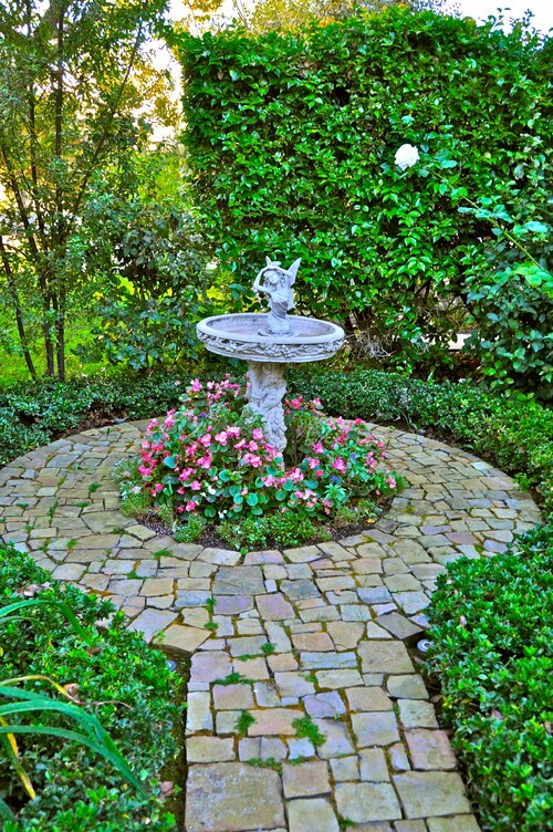 Bird baths sometimes have little adornments attached. Some have birds while others have various animals or some other ornamentation. This bird bath has an angel to keep the birds company.