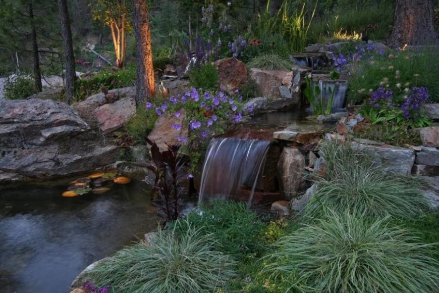 Here, perennials are used around a water feature to give it a more natural look. The plants around this waterfall make it appear as though it may have been found in the wild among the underbrush lined with wildflowers.
