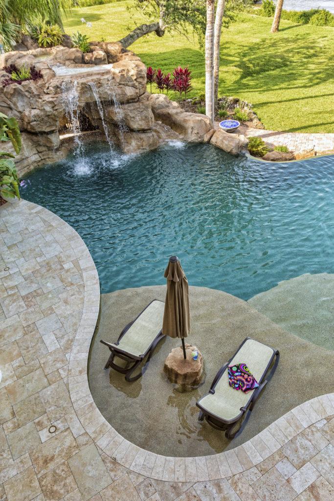 The stone cave and waterfall on the far end of this pool make for an amazing feature in this backyard water park. This is a great place for kids to play and hide. You can really let your imagination run wild in a pool like this.