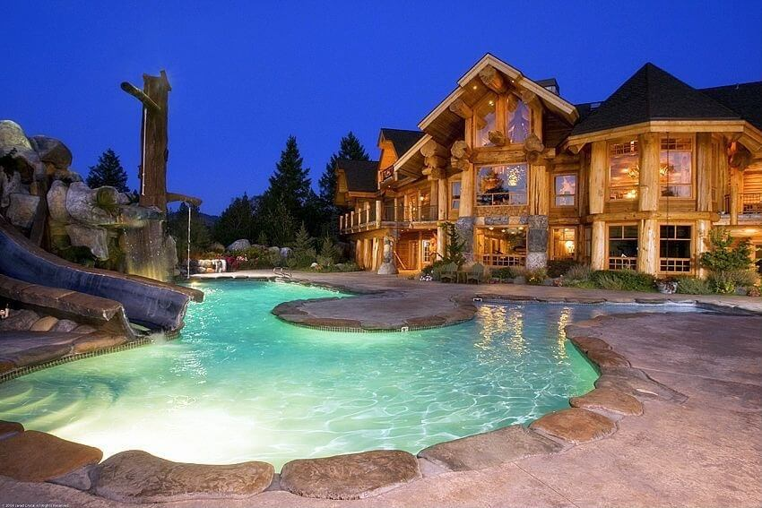 Here is a lovely backyard water park with a well lit pool and a great water slide that has been built into some stone landscaping.