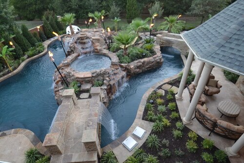 There is an interesting feature attached to this backyard water park. The bridge that goes over the pool also has a waterfall attached. The water pours over the sides of the bridge into the pool making passing over and under the bridge entertaining.