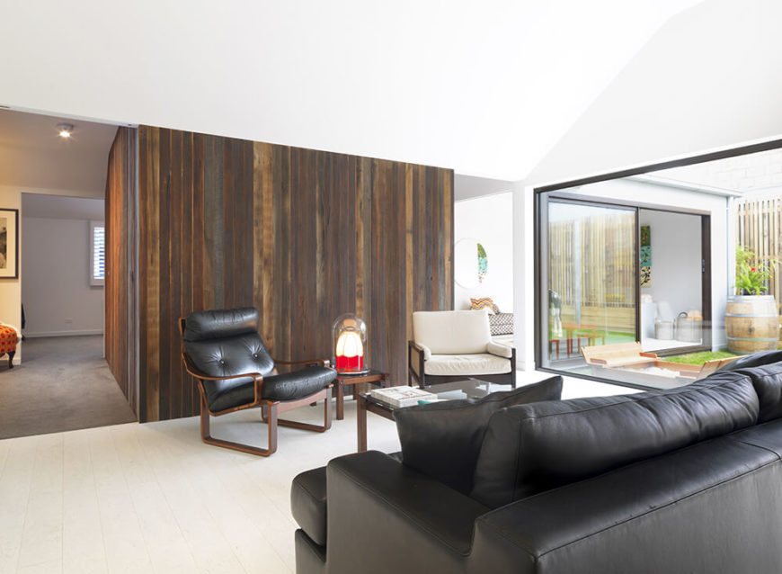 Moving closer to the corner, we see the rich wood paneling in closer view, marking the transition to the more private areas of the home. The living room furniture finds contrast in black leather and sharp midcentury modern style.